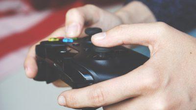 Närbild på två händer som håller i en spelkonsol.