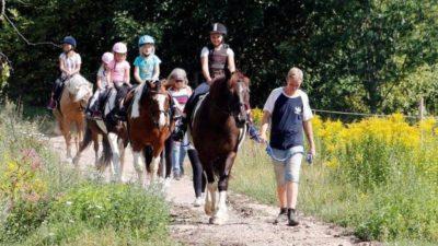 Fyra hästar går på led med barn som rider dem. Två vuxna leder hästarna.