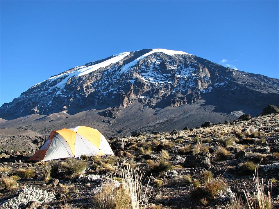 Berget Kilimanjaro är i bakgrunden. Framför Kilimanjaro är ett gult tält på en gräsplätt.