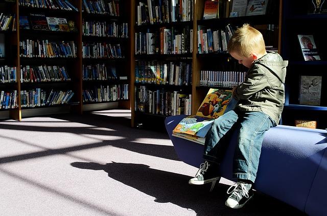 Ett barn sitter på ett bibliotek och bläddrar i en bok.