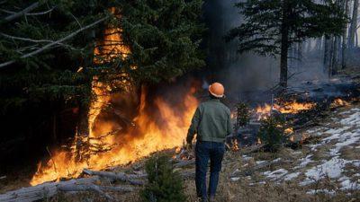 En man i hjälm står framför en skog som brinner.