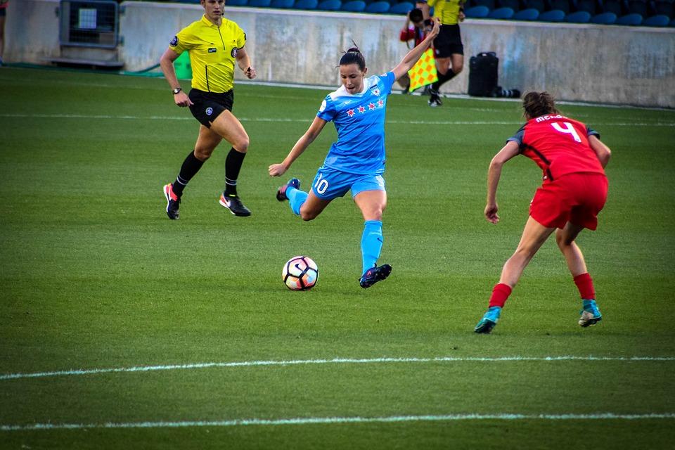 En fotbollsspelare i blåa kläder sparkar på en fotboll