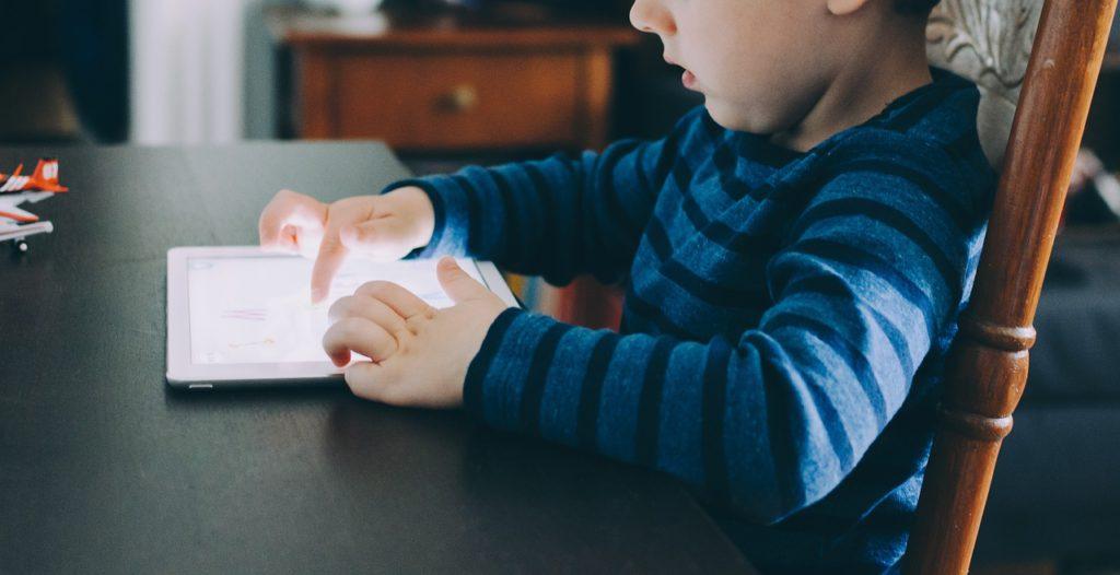 Ett barn sitter och pekar på en läsplatta.