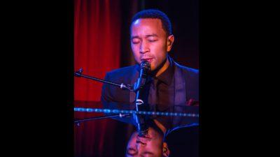 John Legend sitter och sjunger bakom ett piano