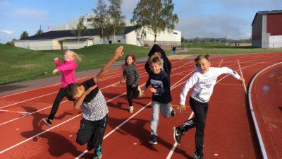Sex barn springer på en löpbana.