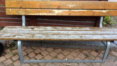 Närbild på en sliten bänk utomhus.