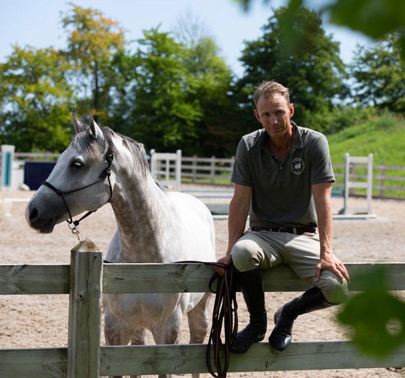 Peder Fredricson sitter på ett staket bredvid sin häst
