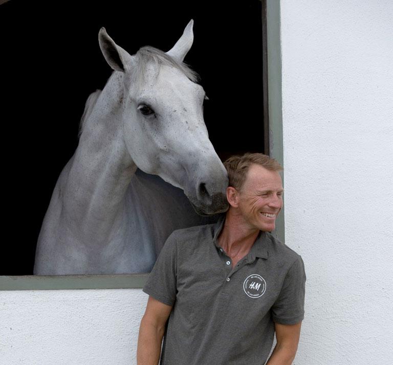 Peder Fredricson ler när en häst nosar på honom