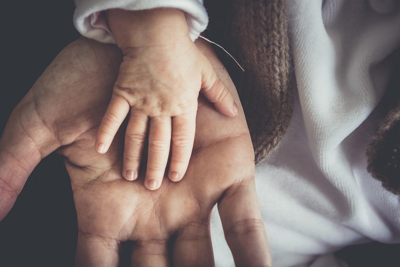 Ett barns hand ligger i en vuxens hand