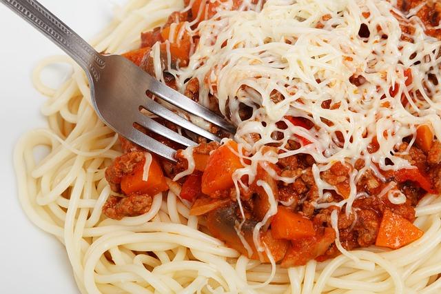 Närbild på pasta med tomatsås och en gaffel.