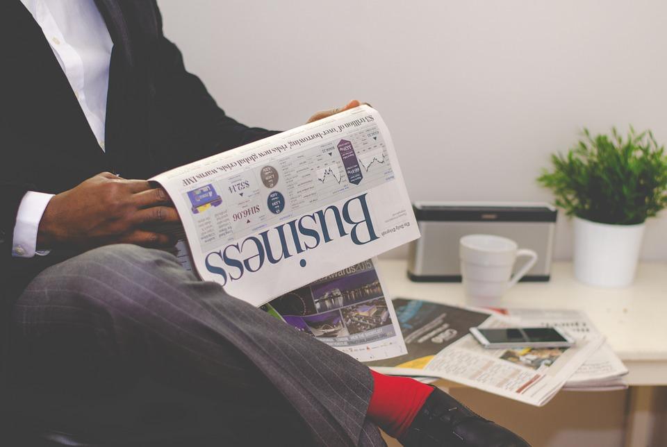En person i kavaj som läser en tidning