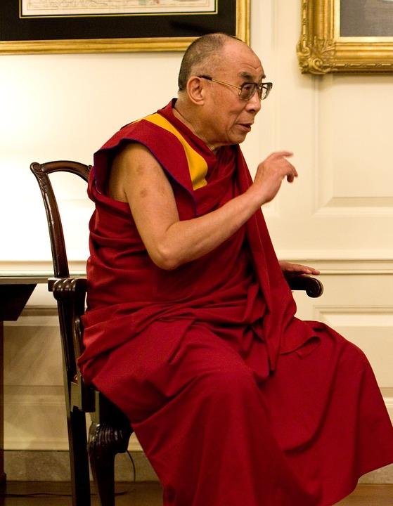 Dalai Lama sitter på en stol i en röd kläsel