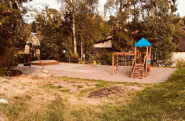 Bild på lekpark omringad av sko, hus och gräs.