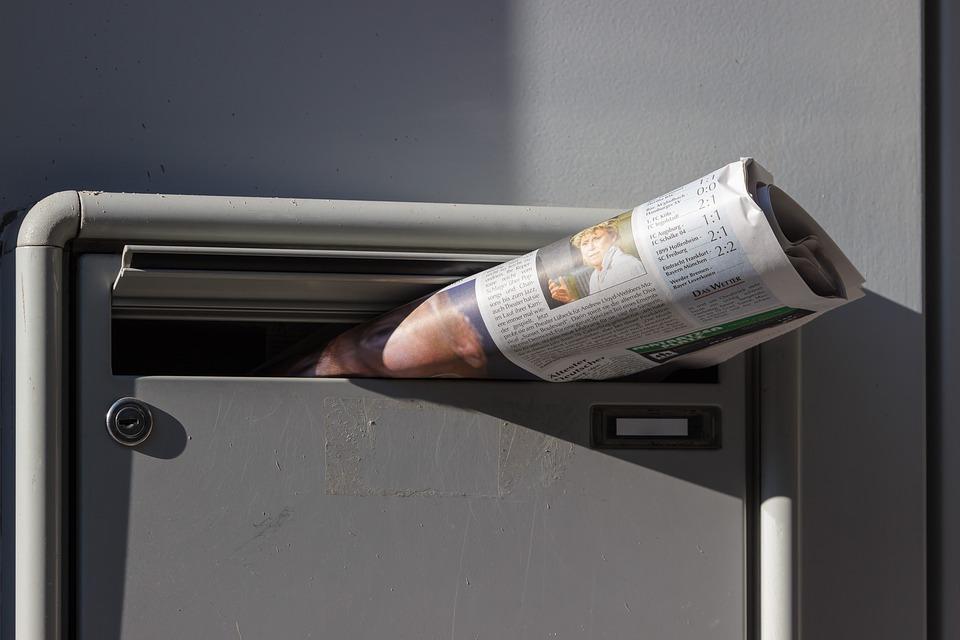 En tidning ligger i en brevlåda