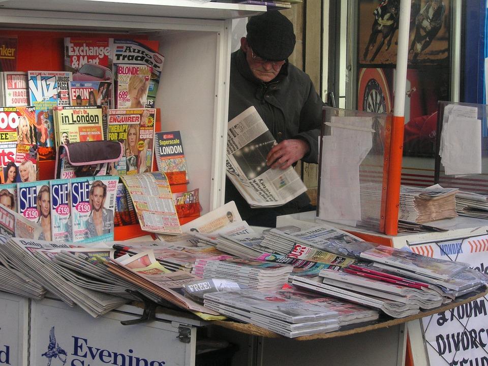 En man står och kollar på flera olika tidningar