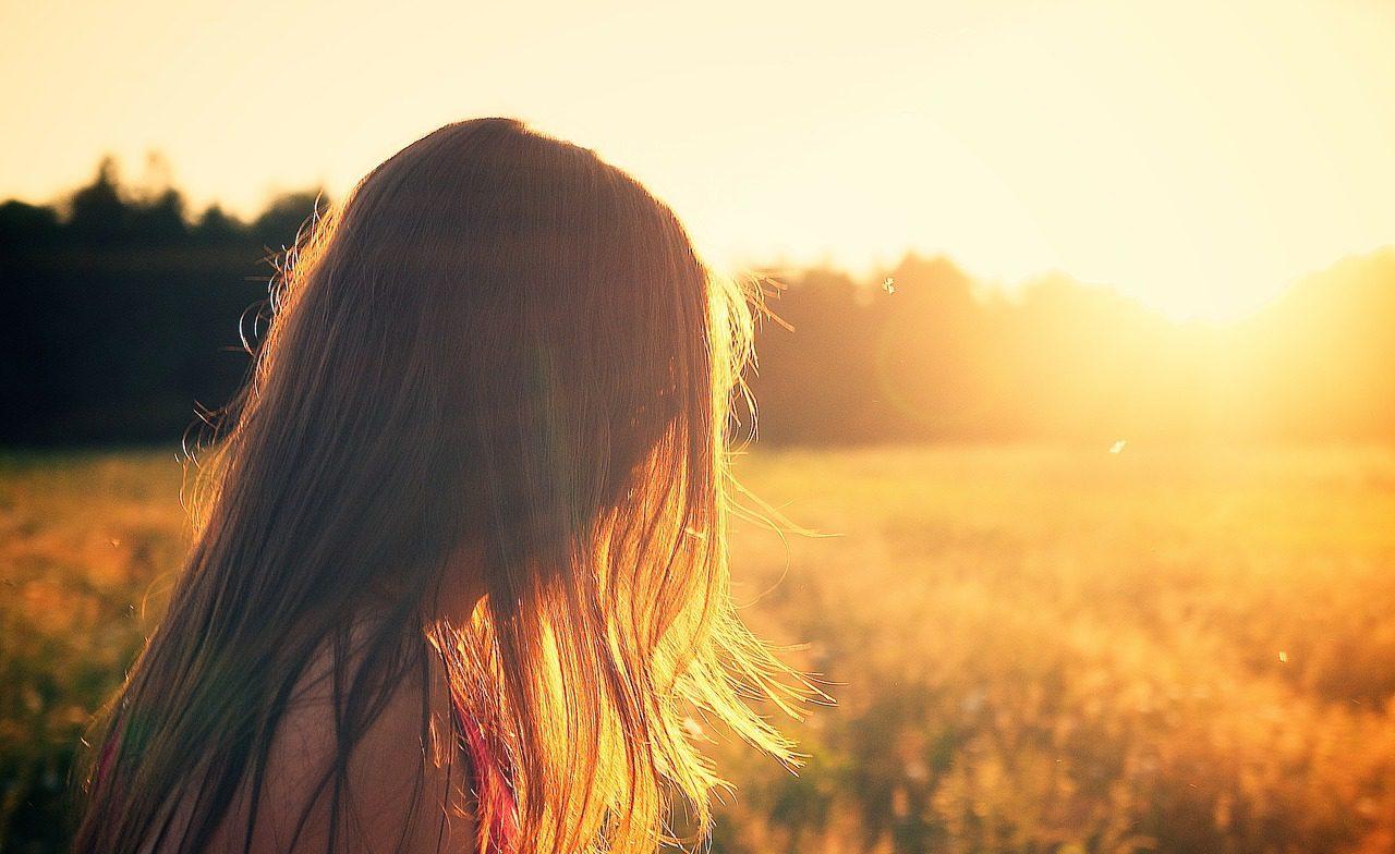 Hon flicka med långt hår som står på ett fält i solnedgången.