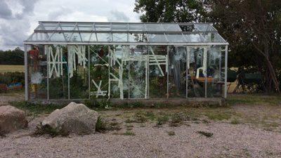 Bild på växthus med krossade rutor.