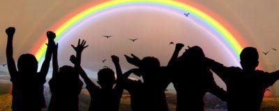 Barns silhuetter står och hejar på en regnbåge