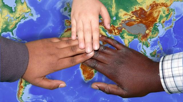 Tre barns händer möts ovanför en karta.