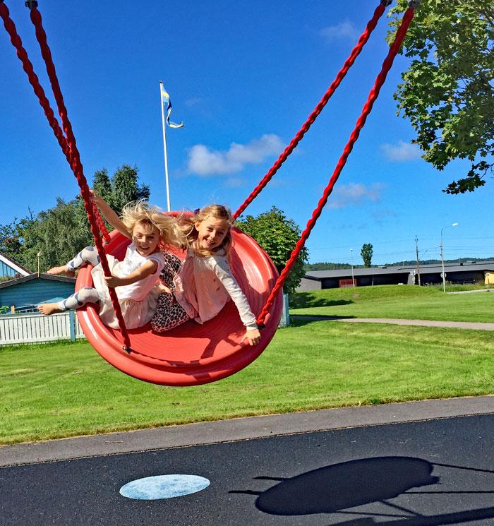 Två barn gungar i en stor gunga och ser glada ut