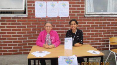 Två elever vid ett bord intill skolans tegelvägg.