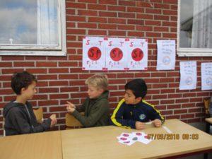 Tre barn vid ett bord intill skolans tegelvägg.