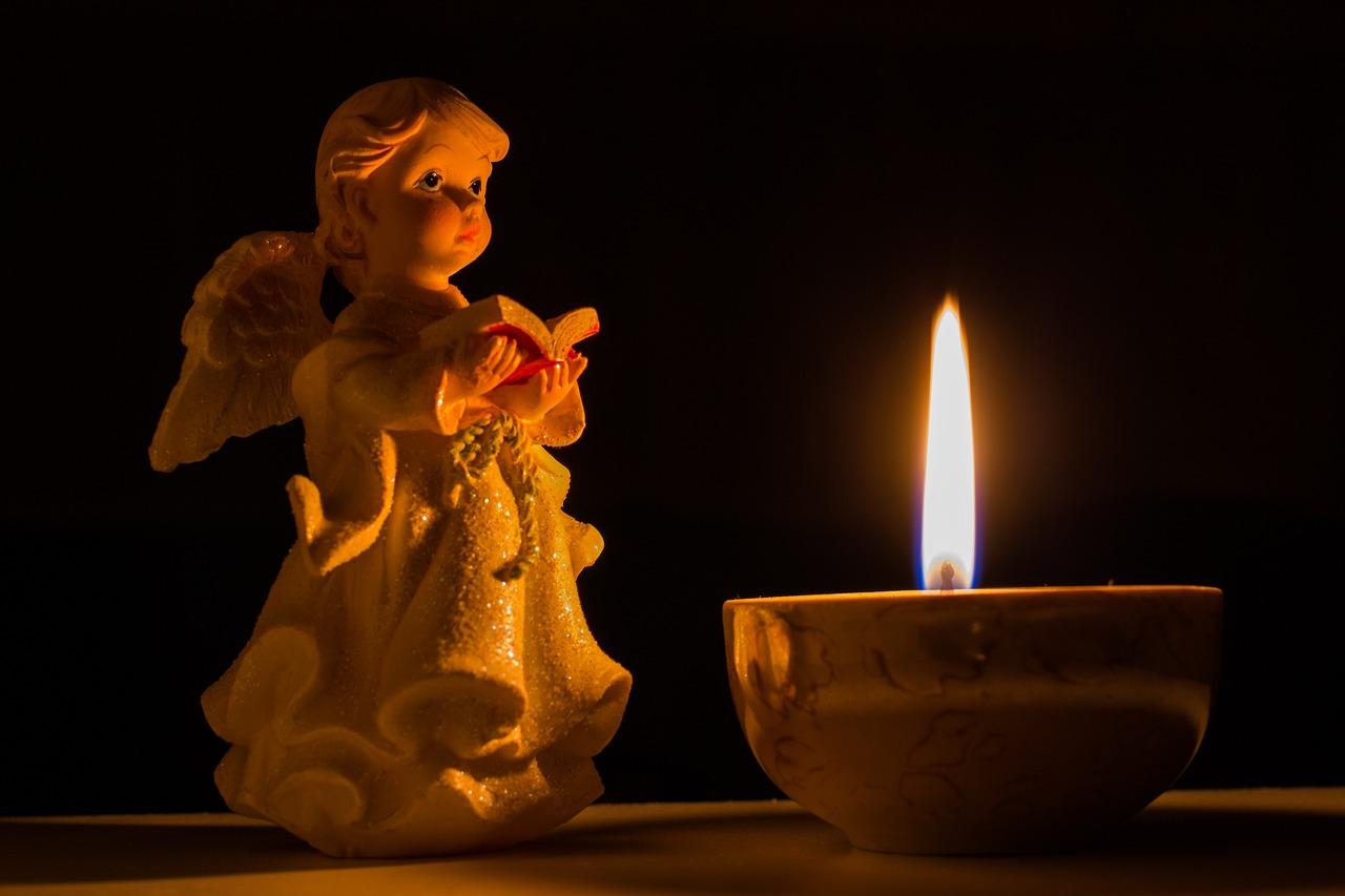 En staty av en ängel och ett tänt ljus