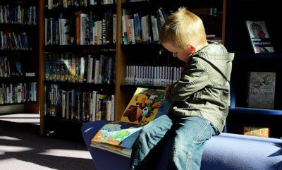 Ett barn som läser en bilderbok på ett bibliotek