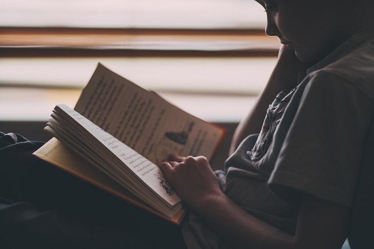 Ett barn läser en bok i mörkret
