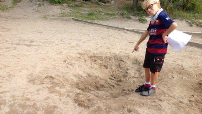 Ett barn pekar ner i en grop i sanden där bilen brukade stå.