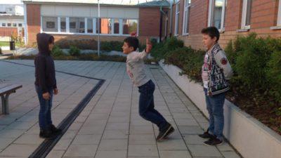 Tre barn leker intill skolbyggnad.