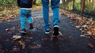 Två par ben promenerar på en höstväg.