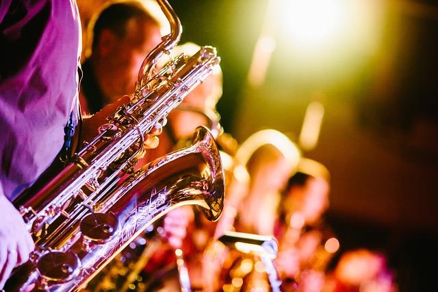 Närbild på en som spelar på saxofon bredvid övriga musikanter på scen.