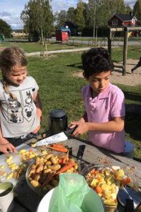 Samir Ahmed och Hanna Ekberg hackar grönsaker.