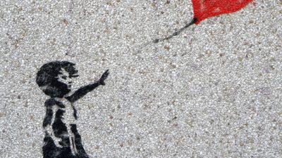 Ett barn som sträcker sig efter en hjärtformad röd ballong är målad på en grå mur.
