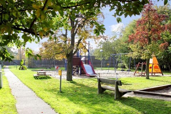 Lekplats med gungor och rutchkana, träd, bänkar och sandlåda.
