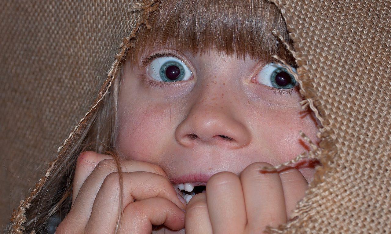 Ett barn tittar ut ur ett hål i ett tyg och ser rädd ut