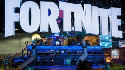 Stora bokstäver som bildar ordet Fortnite hänger ovanför en gammal buss.