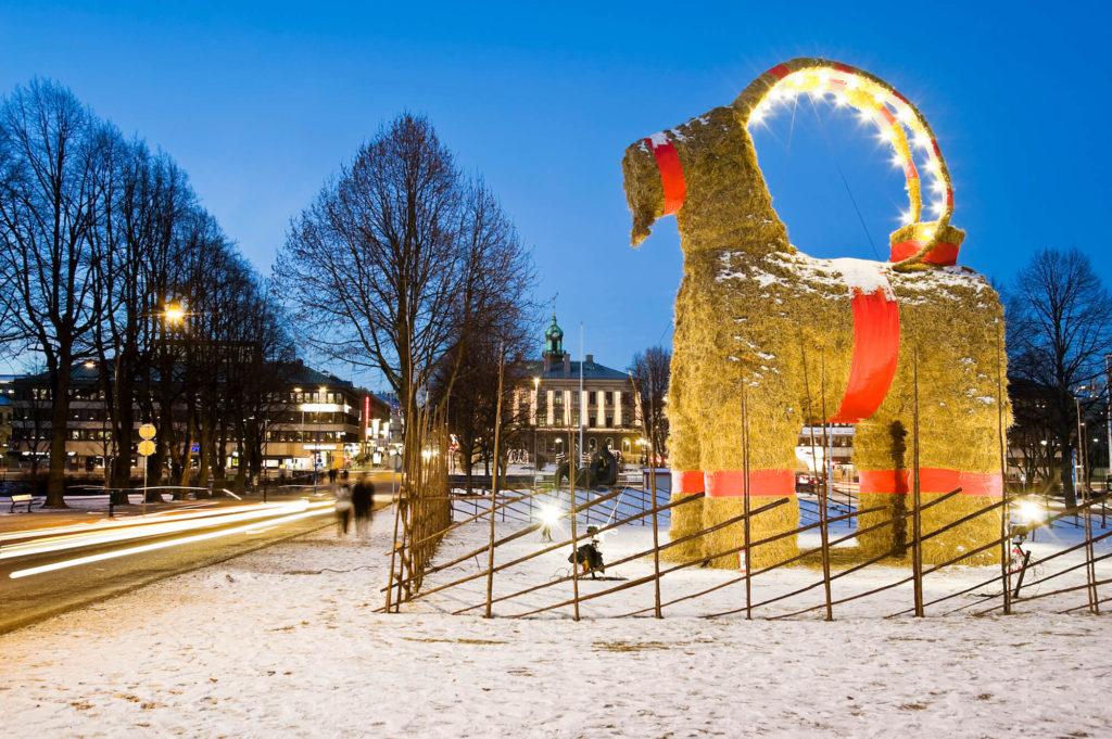 En stor bock av halm står bredvid flera träd. Bocken har röda band runt magen och benen. Runt bocken är det ett staket. På marken är det snö.