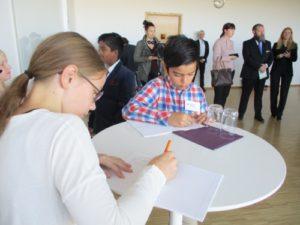Minireportrar står vid ett bord och antecknar frågorna till prinsen.