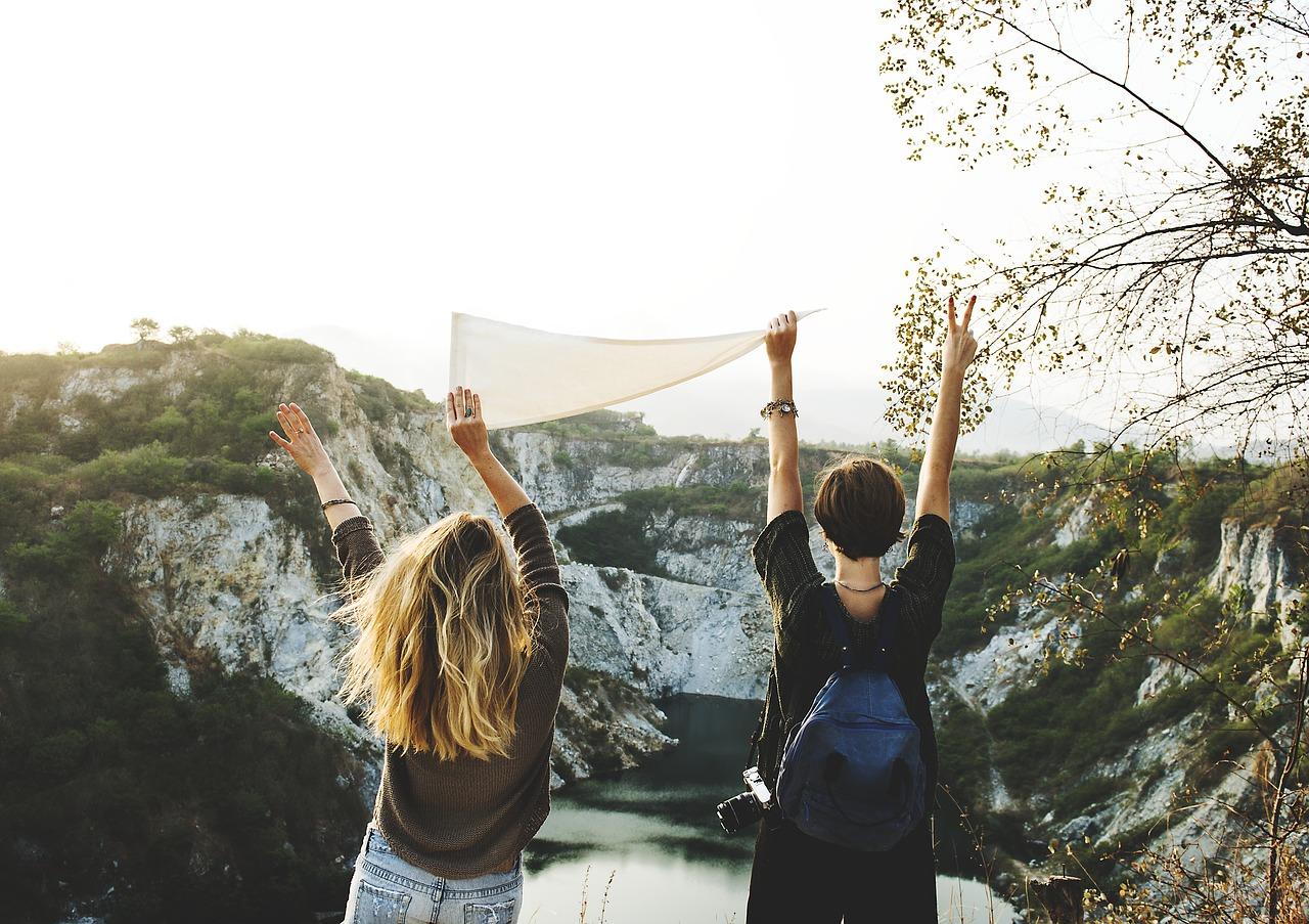 Två personer som syns bakifrån, de håller upp en vit flagga. I bakgrunden syns en sjö och berg.