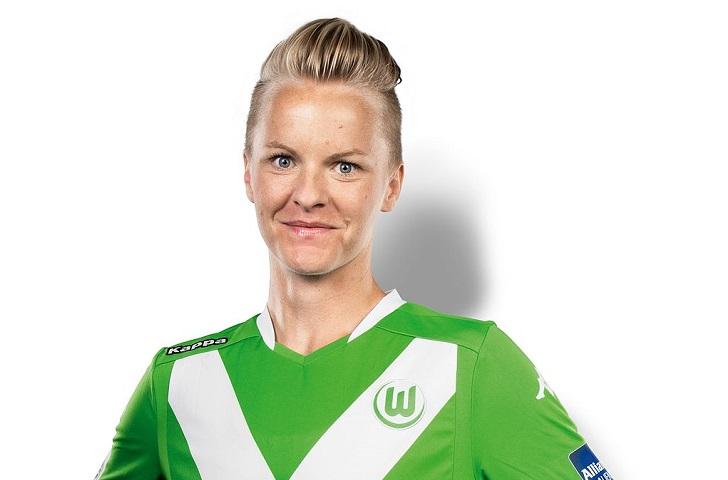 Nilla står mot en vit vägg och ler mot kameran. Hon har en grön fotbollströja och har kort hår som är bakåtkammat.