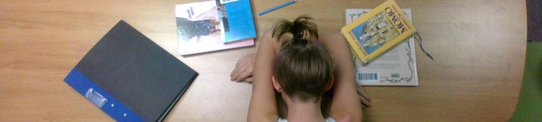 En flicka ligger med huvudet i armarna påen bänk med utspridda böcker.