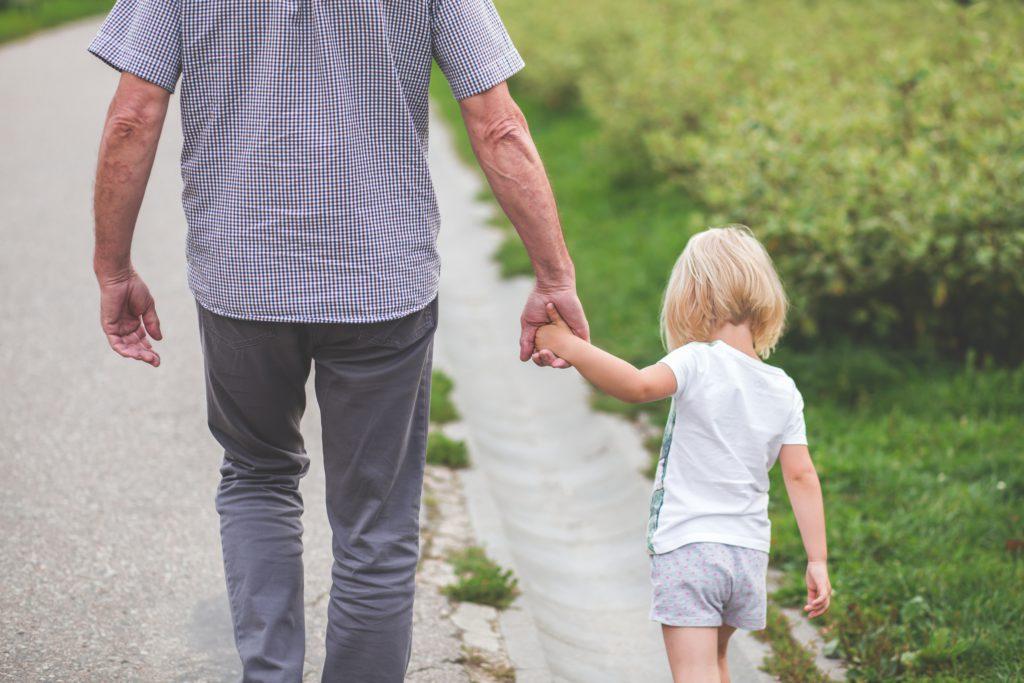En gammal man och ett barn går hand i hand.