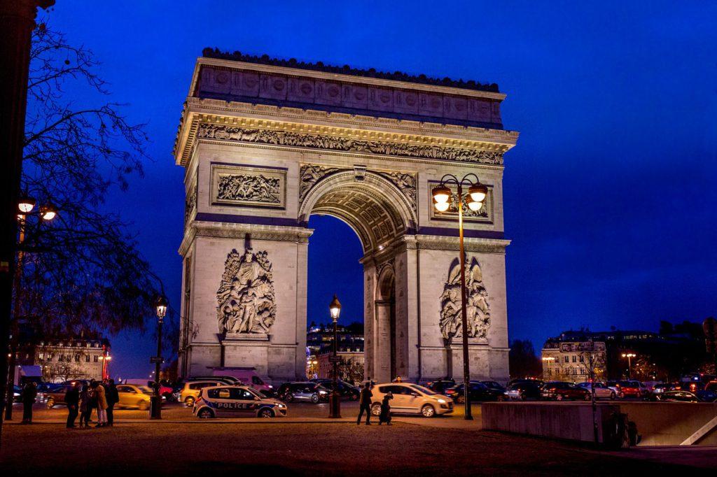 Triumfbågen är upplyst på kvällen. Det är en stor båge av sten, med statyer på sidorna.