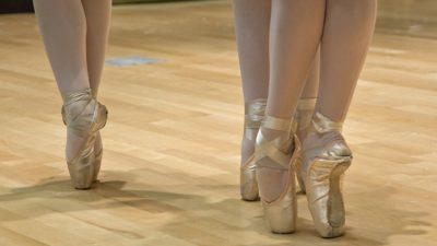 Balettdansare står på tå i balettskor.