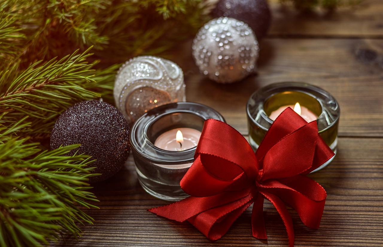 Två ljusstakar med ljus i som brinner. Bredvid ligger en rosett, flera julkulor och lite grankvistar.