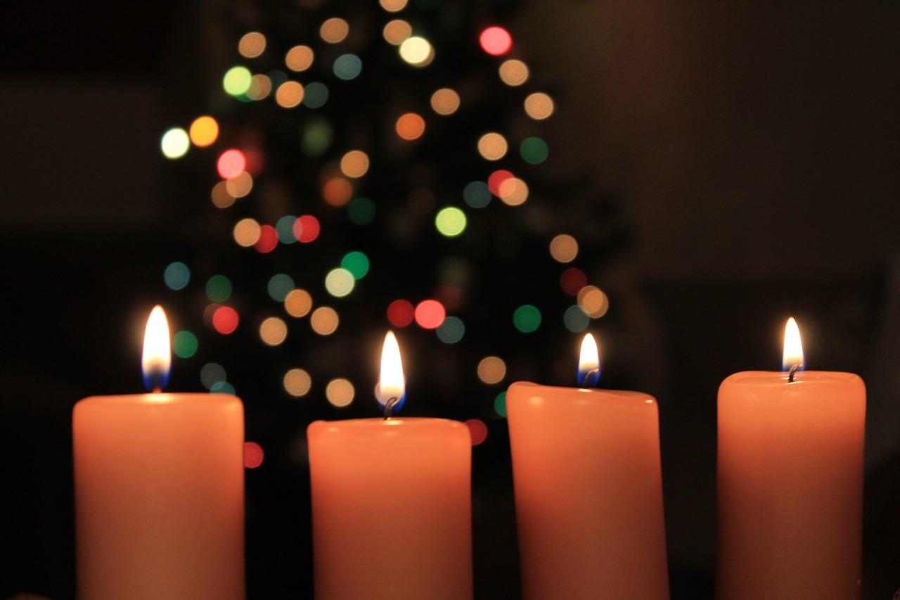Fyra ljus brinner. I bakgrunden syns en julgran med julgransljus i.