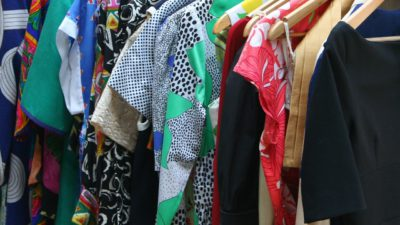 Förgglada kläder som hänger på galgar i rad