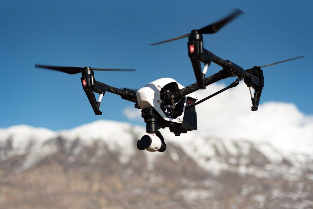 """En liten maskin flyger i luften. Den har en """"kropp"""" och två propellrar som sitter på två pinnar."""